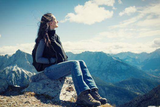 Woman on mountain hike having rest sitting on rock