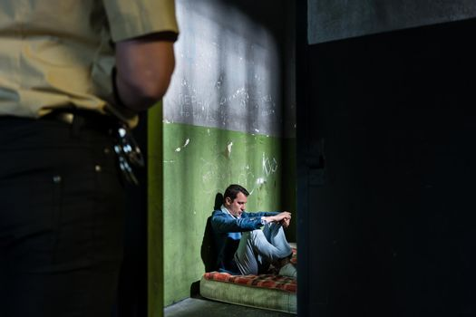 Young male prisoner sitting alone in an obsolete prison cell gua