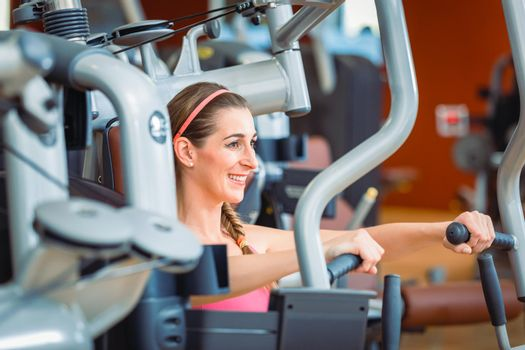 Side view of a cheerful woman exercising during upper-body workout