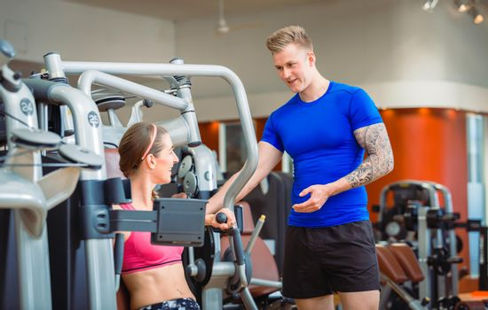 Handsome personal trainer guiding a beautiful woman at a modern fitness