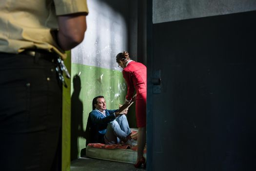 Dedicated female attorney visiting a young inmate in an obsolete prison cell