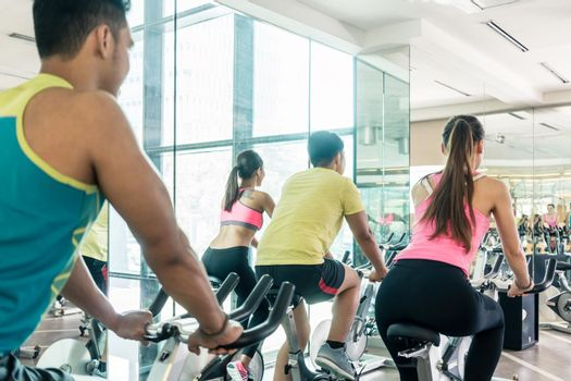 Fit women burning calories during indoor cycling class