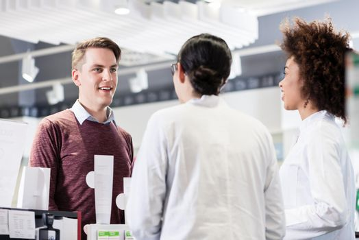 Happy customer talking with two helpful pharmacists in a contemp