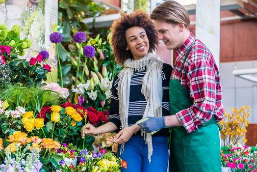 Beautiful woman buying freesias at the advice of a helpful vendor
