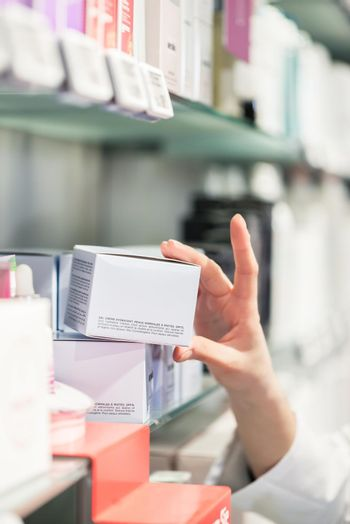Close-up of the hand of female pharmacist picking up the best product