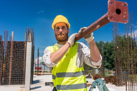 Blue-collar worker carrying a heavy metallic bar during work