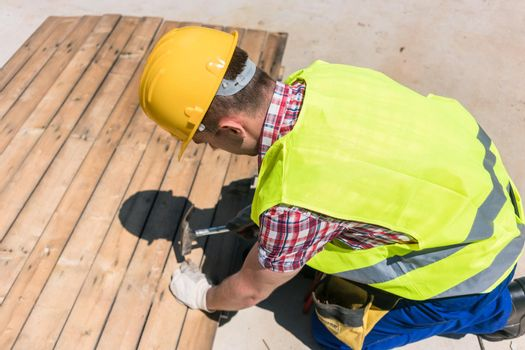 High-angle view of a blue-collar worker using a hammer on the co