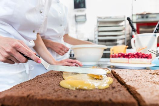 Confectioner woman getting chocolate cake ready with topping