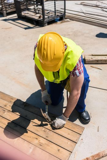 High-angle view of a blue-collar worker using a hammer