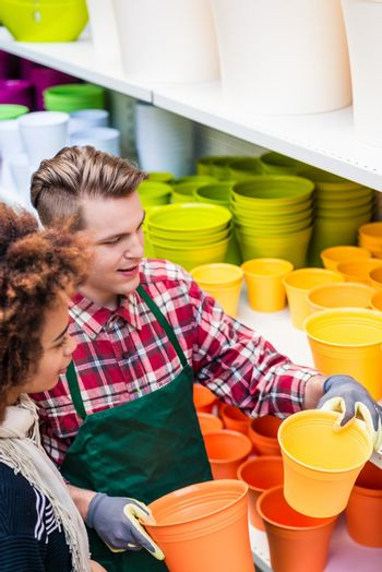 Customer buying plastic pots at the advice of a helpful worker