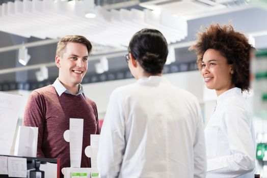 Happy customer talking with two helpful pharmacists in a contemporary drugstore