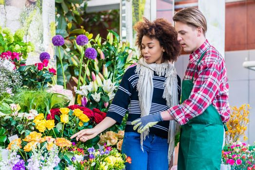 Beautiful woman buying freesias at the advice of a helpful vendo