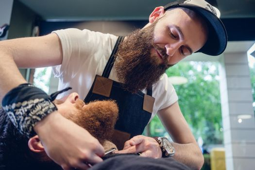 Bearded young man ready for shaving in the hair salon of a skill