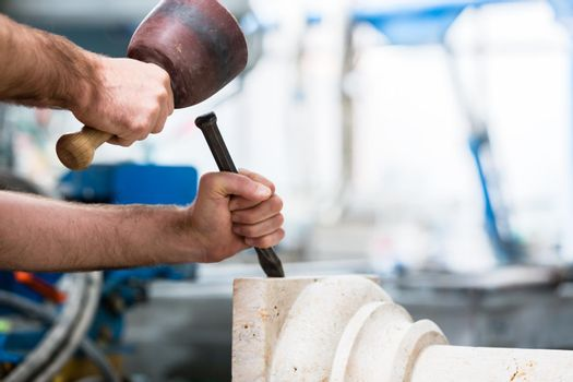 Stonemason working at marble pillar