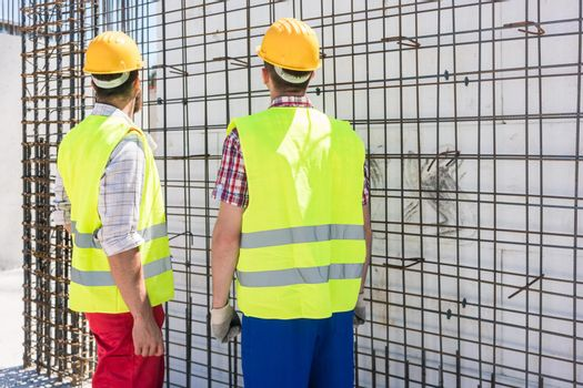 Two workers checking the durability of the steel structure of a