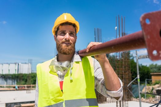 Blue-collar worker carrying a heavy metallic bar during work on