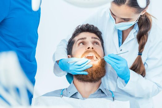 Reliable dentist using sterile instruments while cleaning the te