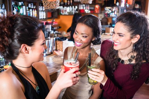Girls enjoying nightlife in a club, drinking cocktails