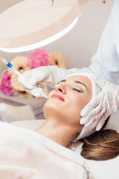 Beautiful woman relaxing during non-invasive facial treatment