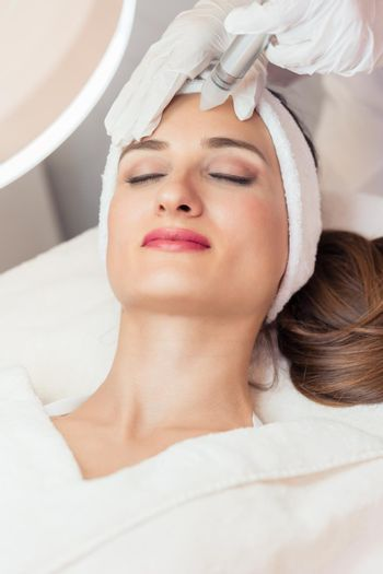 Close-up of the face of a beautiful woman smiling during facial treatment