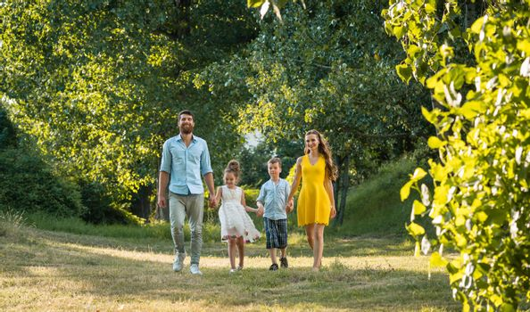 Happy family with two children holding hands during recreational walk