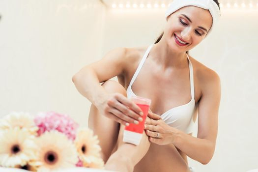 Fit woman waxing her legs with a portable roll-on depilatory wax