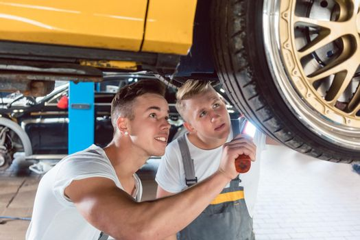 Two dedicated auto mechanics tuning a car through the modification of the rims