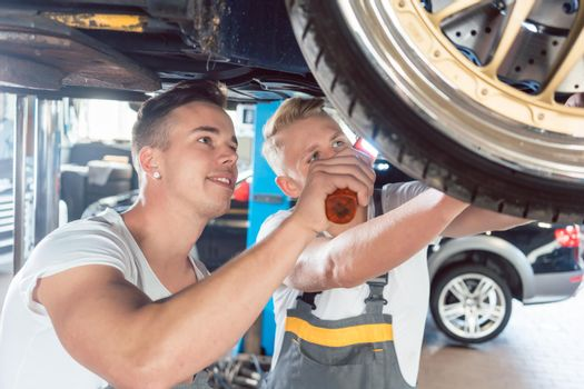 Two dedicated auto mechanics tuning a car