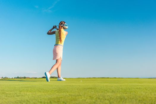 Professional female golf player smiling while swinging a driver