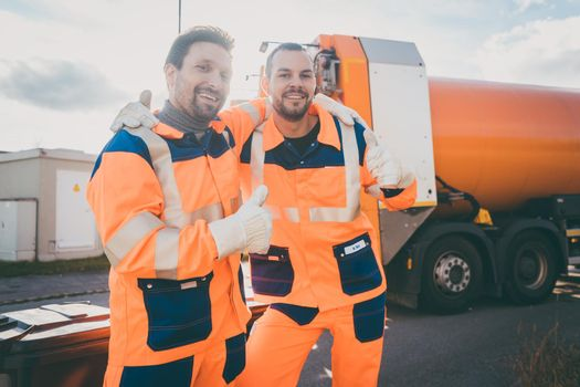 Garbage removal workers giving a thumbs-up