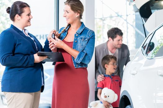 Family buying new car in auto dealer showroom
