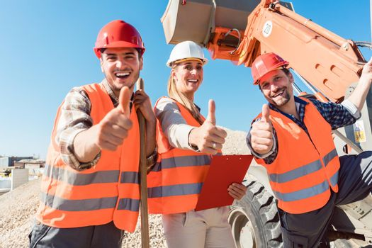 Construction workers and civil engineer showing thumbs up