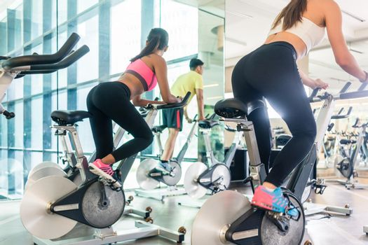 Fit women burning calories during indoor cycling class in a mode