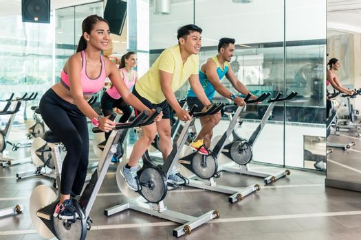 Fit women burning calories during indoor cycling class in a fitness club