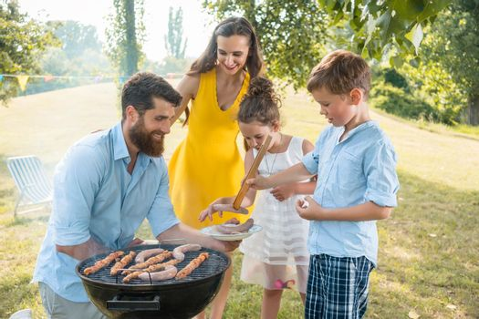 Dedicated father helping son to use wooden tongs during family picnic