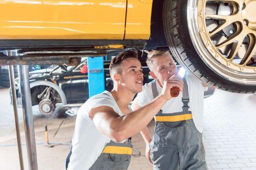 Two dedicated auto mechanics tuning a car through the modificati