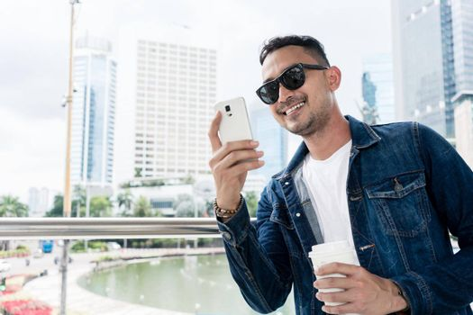 Portrait of a trendy young man smiling during online communication on his smartphone, outdoors while visiting a modern city