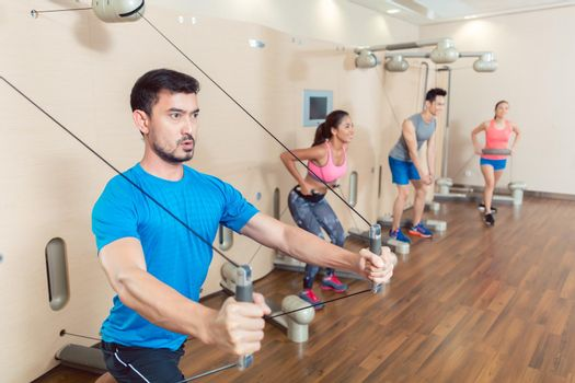 Determined young man exercising with resistance bands