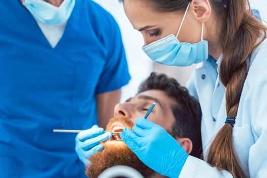 Reliable dentist using sterile instruments while cleaning teeth