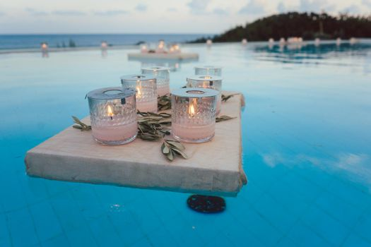 Candles floating in swimming pool at beach house party