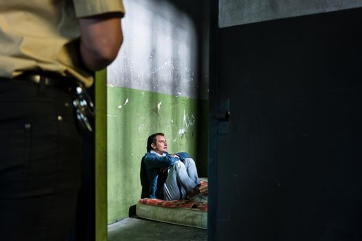 Young male prisoner sitting alone in an obsolete prison cell guarded by a police officer