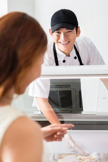 Smiling helpful assistant serving a customer