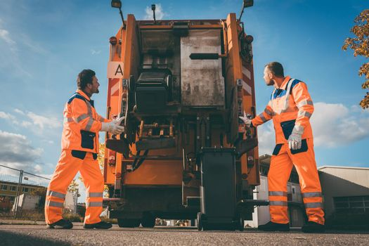 Two refuse collection workers loading garbage into waste truck