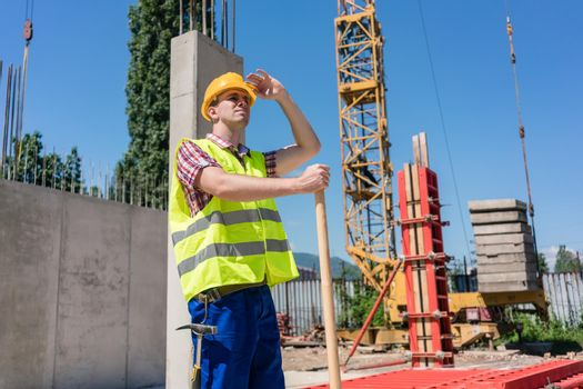 Young blue-collar worker looking up with a worried facial expression