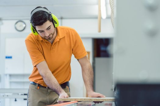 Carpenter working in furniture factory on machine