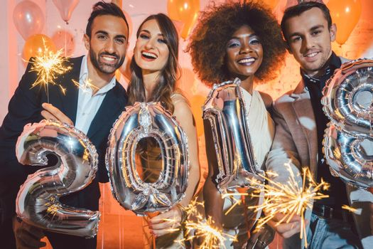 Group of party people celebrating the arrival of 2018