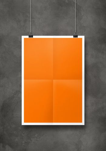 Orange folded poster hanging on a concrete wall with clips