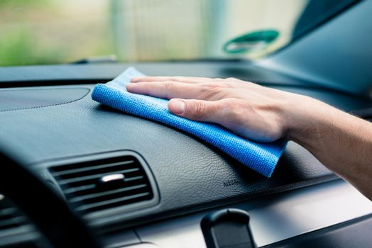 Man wiping the dashboard of his car