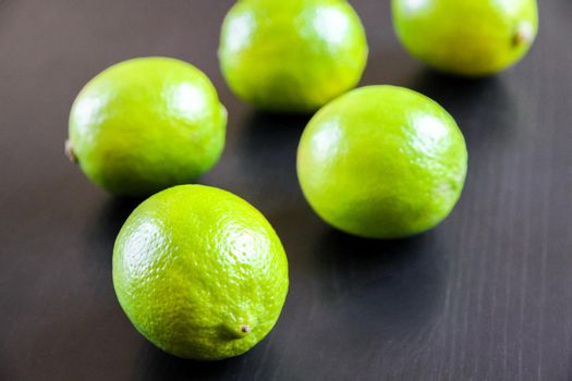 Group of fresh organic limes on a black background