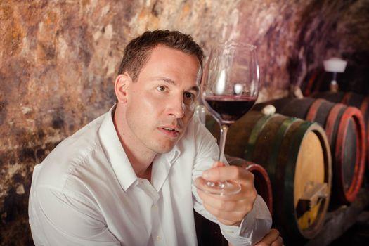 man having wine tasting in cellar